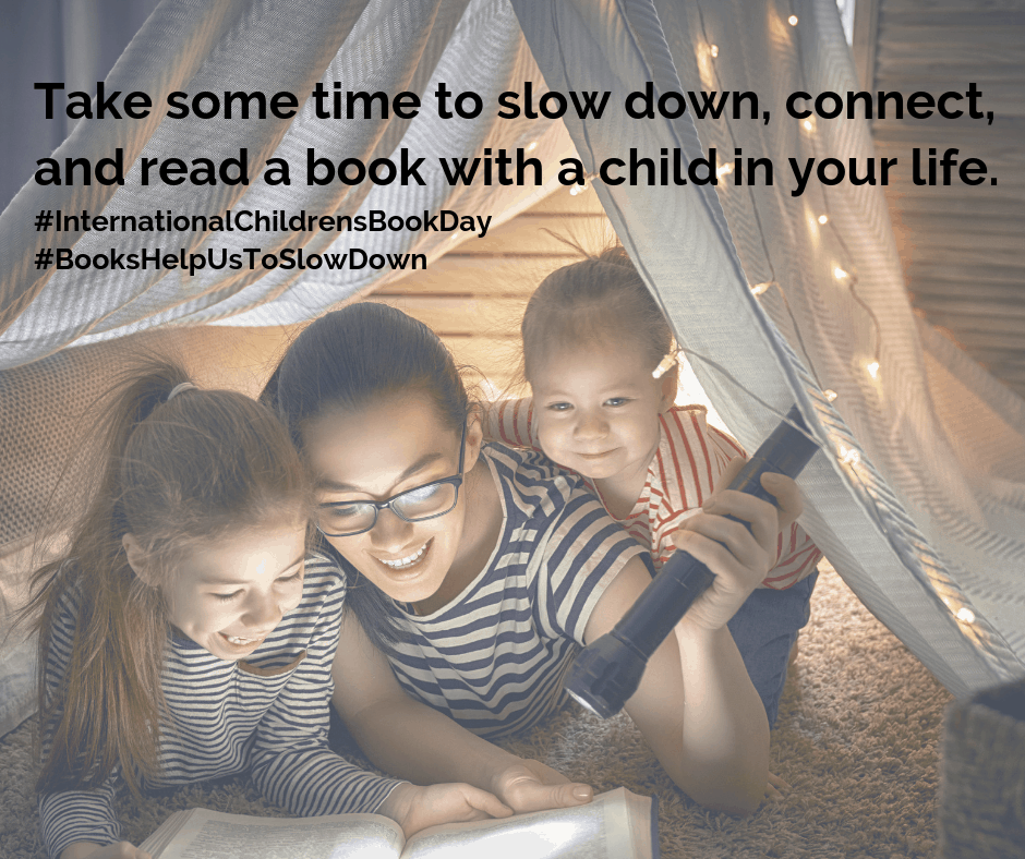"Parent and two children reading books in a blanket fort. Text over image reads ""Take some time to slow down, connect, and read a book with a child in your life"" #InternationalChildrensBookDay #BooksHelpUsToSlowDown"